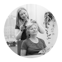 a woman brushing the hair of an elder